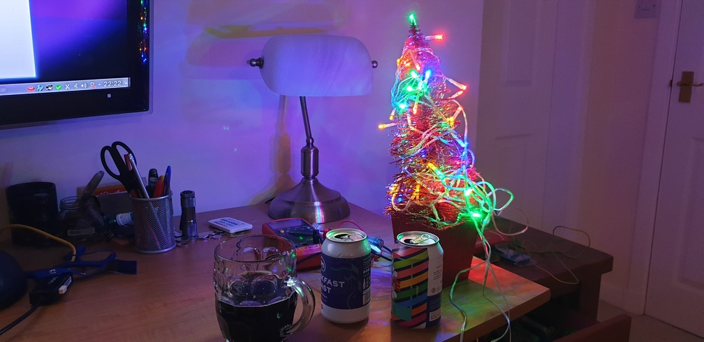 A small Christmas on a desk with some beer.